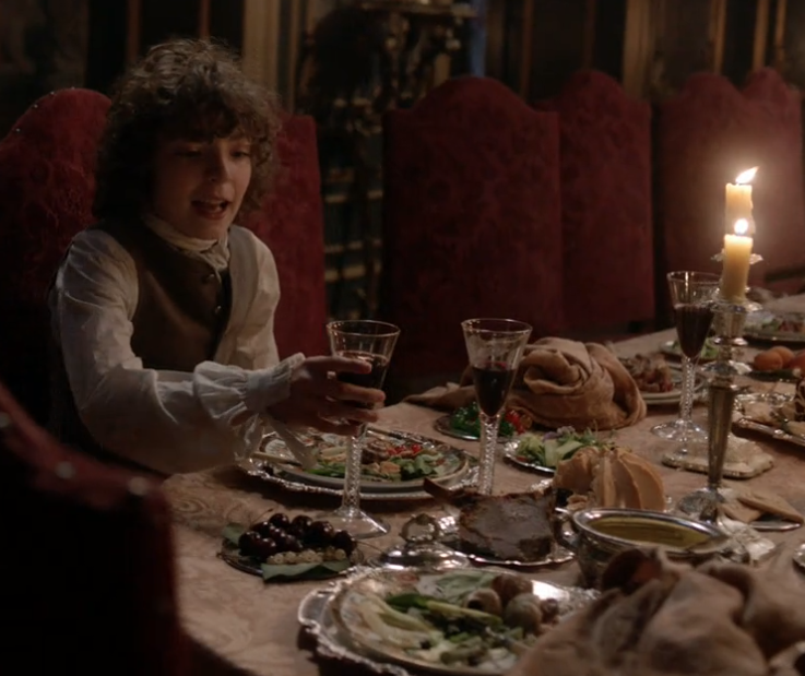 Fergus enjoys the remains of dinner in Outlander Season 2