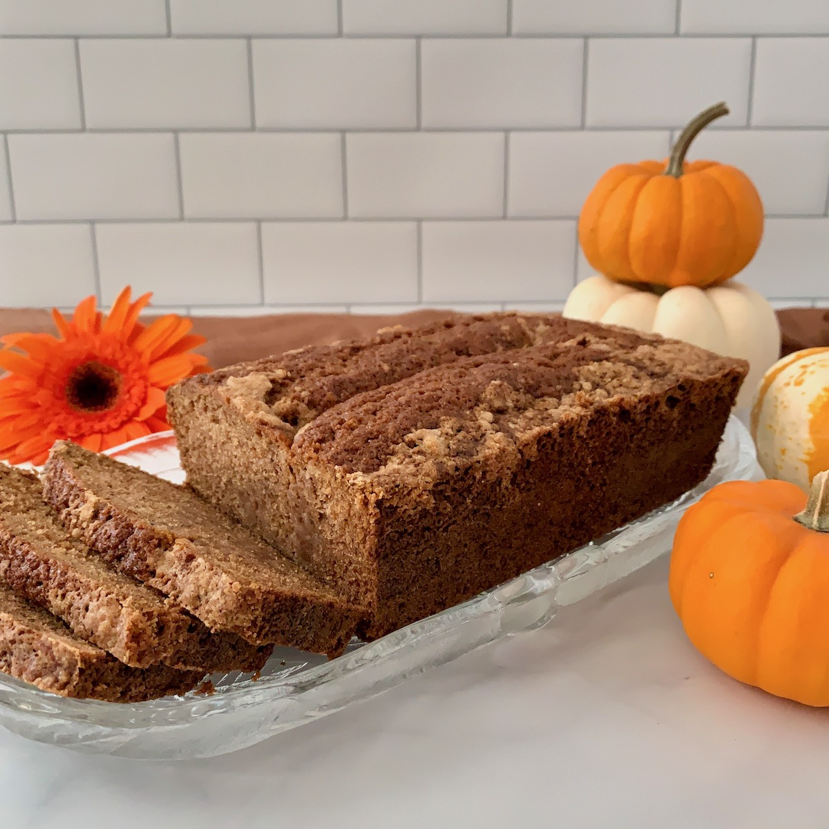 Sourdough Spice Cake sliced on plate with pumpkins