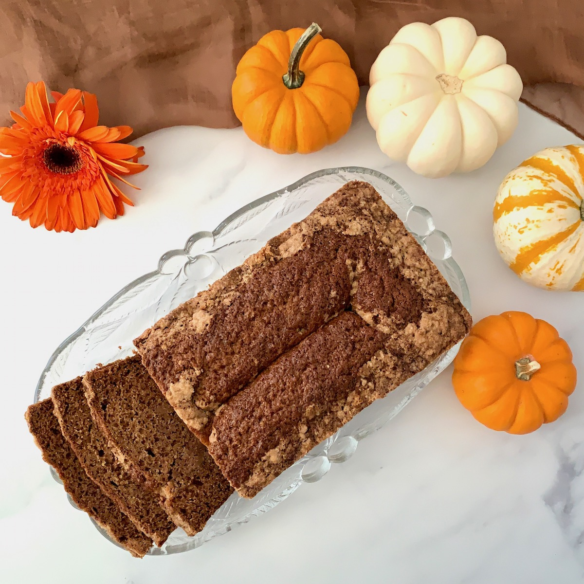 Sourdough Spice Cake sliced on plate with pumpkins overhead