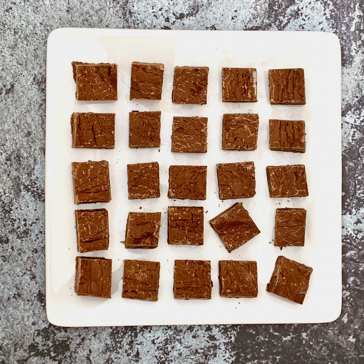 dark chocolate whisky fudge laid out on a square plate overhead